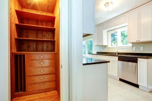 White ktichen room with wooden closet. Small closet with storage shelves and drawers